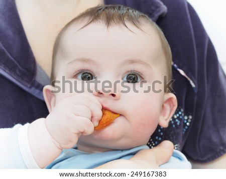 Portrait of little caucasian baby boy eating dried apricot  - stock photo
