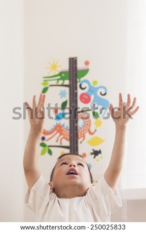 Portrait of Little Caucasian Boy Using Wall Ruler for Making Height Measurements. Vertical Shot - stock photo