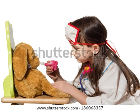 Portrait of little caucasian girl in medical costume dripping nose of rabbit toy isolated on white - stock photo