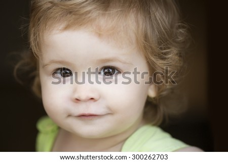 Portrait of little curious smiling male kid with blond curly hair looking forward outdoor on dark background, horizontal picture - stock photo