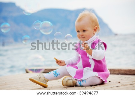 Portrait of little cute baby girl looking on soap bubbles on berth near sea - stock photo