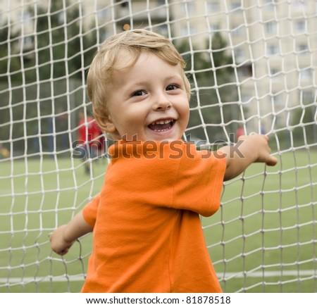 portrait of little cute boy on football field - stock photo