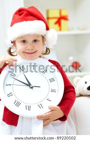 Portrait of little cute girl holding big white clock - stock photo