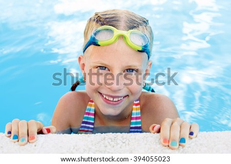 Portrait of little cute girl in the swimming pool. Sunny summer day - stock photo