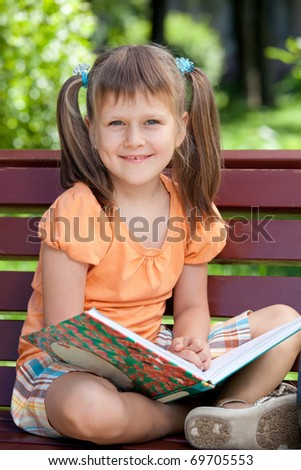 Portrait of little cute smiling girl preschooler with open book who is sitting cross-legged on the wooden bench in summer park - stock photo