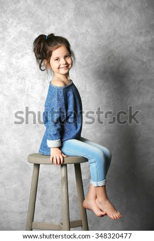 Portrait of little fashion kid girl on gray wall background - stock photo
