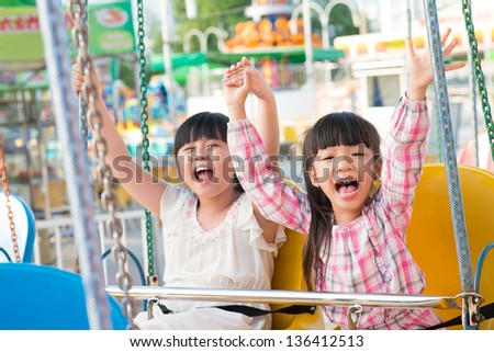 Portrait of little friends sitting on chain swing and raising hands in excitement - stock photo