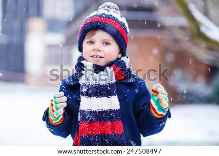 Portrait of little funny boy in colorful winter clothes having fun with snow, outdoors during snowfall. Active outdoors leisure with children in winter. Kid with warm hat, hand gloves and scarf  - stock photo