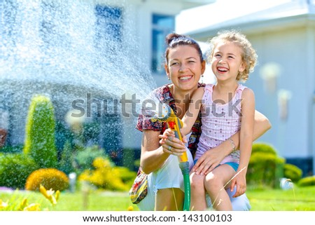 Portrait of little gardener girl with mother watering flowers on the lawn near cottage. - stock photo