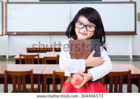 Portrait of little girl back to school and standing in the classroom while wearing glasses and holding a book with apple - stock photo