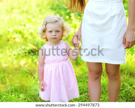 Portrait of little girl child, daughter holds hand mother - stock photo