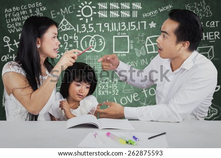 Portrait of little girl crying while her parents quarreling when help their child to study - stock photo