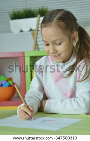Portrait of Little girl drawing at home - stock photo