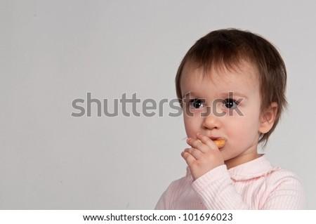 Portrait of little girl eating snacks - stock photo