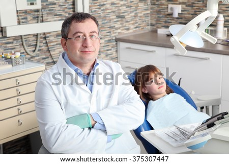 Portrait of little girl has a dental examination. Male dentist with arms crossed and his smiling child patient sitting at dentist office.  - stock photo