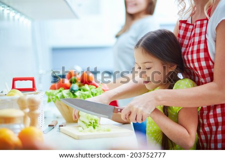 Portrait of little girl helping her mother to cook in the kitchen - stock photo