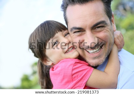 Portrait of little girl hugging her daddy - stock photo