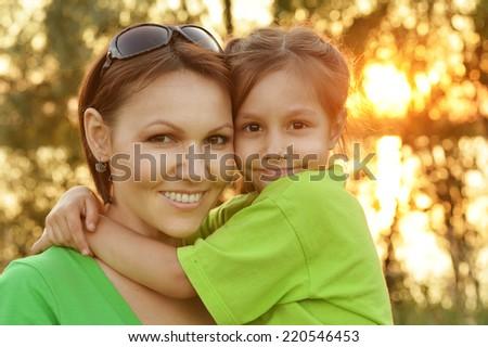 Portrait of  little girl hugging her mother - stock photo