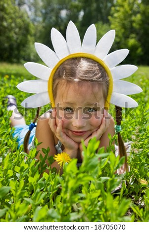 Portrait of little girl in camomile hat on green grass in a sunny day - stock photo
