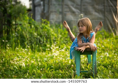 Portrait of little girl in the yard of a country house - stock photo