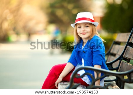 Portrait of little girl on bench in a park, leisure the nature. Close-up. Happiness, fashionable concept. - stock photo