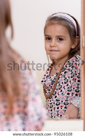 Portrait of little girl. Reflection in the mirror. - stock photo