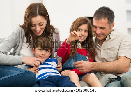 Portrait Of Little Girl Sitting On Couch With Family Showing Key Of New House - stock photo