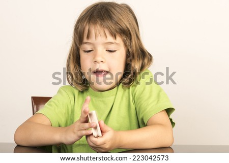 portrait of little girl smiling while shuffling some cards - stock photo