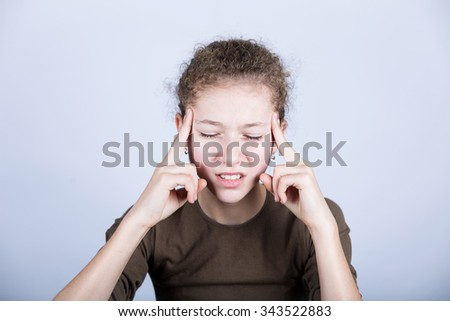 Portrait of little girl suffering from headache and holding hands on her head.Stressed little girl having problems. - stock photo