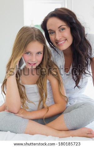 Portrait of little girl using mobile phone while sitting with mother in bed at home - stock photo