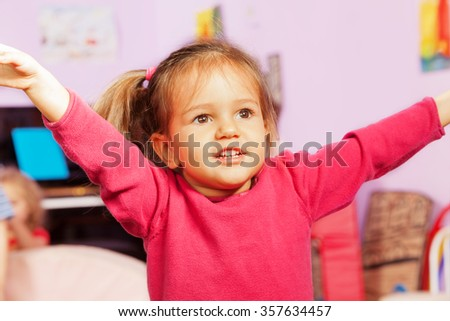 Portrait of little girl with lifted hands  - stock photo