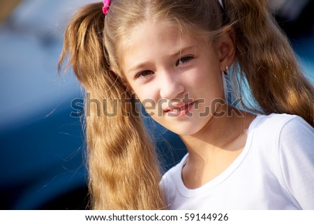 portrait of  little girl with long hair,smiling at the camera the blue - stock photo
