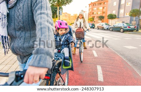 Portrait of little girl with security helmet on the head sitting in bike seat and her mother with bicycle on the background. Safe and child protection concept. - stock photo