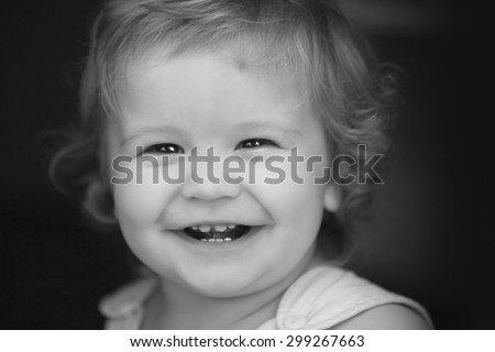 Portrait of little laughing pretty male kid with curly hair looking forward outdoor on dark background black and white closeup, horizontal picture - stock photo