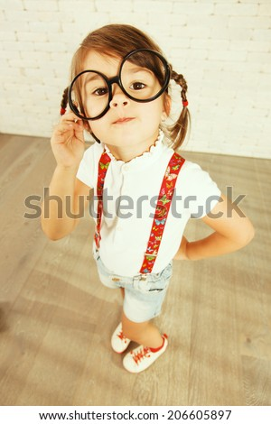 Portrait of little nerd girl looking at camera with big eyes wearing glasses.  - stock photo