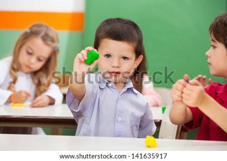 Portrait of little preschool boy showing clay with friends in background at classroom - stock photo