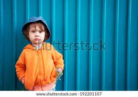 Portrait of little pretty girl on blue fence background - stock photo