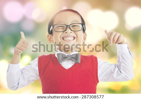Portrait of little schoolboy showing thumbs up on the camera, shot with light glitter background - stock photo