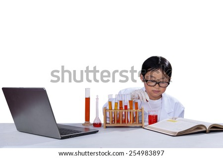 Portrait of little schoolboy wearing lab coat and doing research, isolated over white background - stock photo