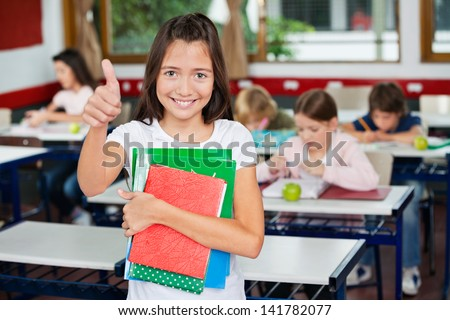 Portrait of little schoolgirl gesturing thumbs up while holding books with classmates studying in background - stock photo