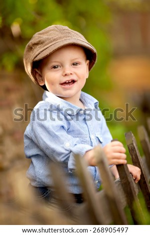portrait of little smiling boy in the blue shirt and brown cap is standing near the wooden fence in the garden - stock photo