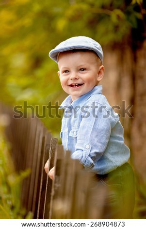 portrait of little smiling boy in the blue shirt and  cap is standing near the wooden fence in the garden - stock photo