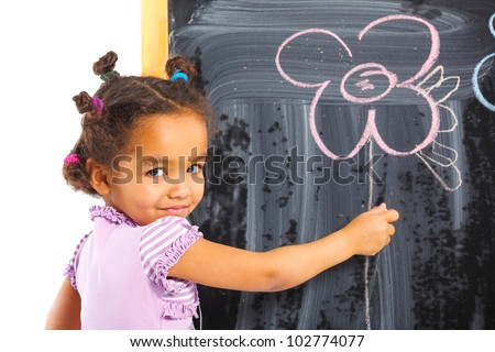 Portrait of llittle mulatto girl is drawing on a blackboard. Isolated on white background - stock photo
