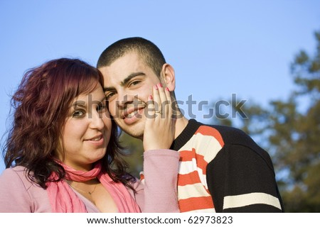 Portrait of love couple embracing outdoor in park looking happy - stock photo