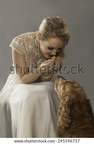 Portrait of lovely blonde girl holding a treat for her cute spaniel dog - stock photo