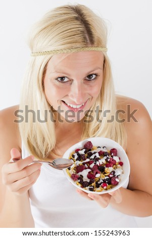 Portrait of lovely blonde woman eating cereals with fruit at breakfast. - stock photo