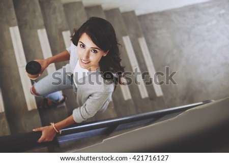 Portrait of lovely brunette walking up the stair, view from above - stock photo