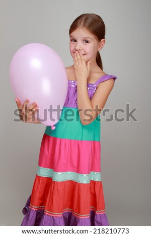 Portrait of lovely cheerful little girl with a sweet smile played with a balloon on gray background/Girl with a pink air balloon on Holiday - stock photo
