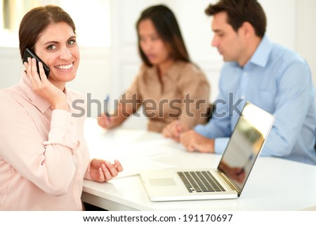 Portrait of lovely executive lady talking on her cellphone while smiling at you and sitting with coworker couple on office desk - stock photo