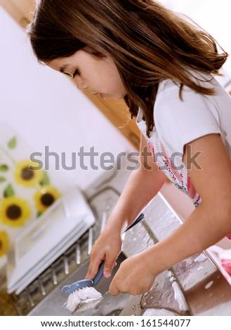 Portrait of lovely girl doing crockery - stock photo
